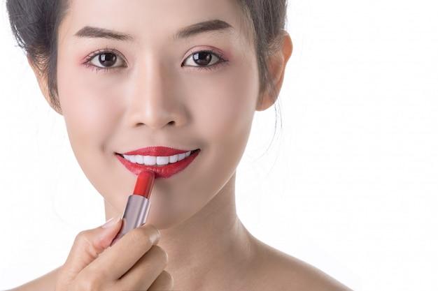 Bella giovane donna asiatica che usando libstick e cosmetici sul proprio viso