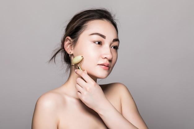 Bella giovane donna asiatica che usando un rullo del fronte della giada sulla sua pelle perfetta. primo piano del viso di bellezza. concettuale di trattamenti per il viso con pietre semi preziose. isolato su grigio con spazio di copia