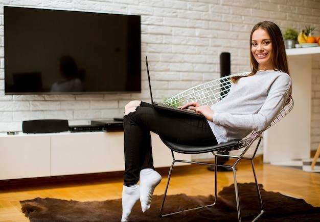 Bella giovane donna asiatica con il sorriso felice che si rilassa mentre sedendosi sulla sedia in salone