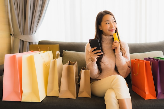 Bella giovane donna asiatica del ritratto che per mezzo del computer portatile o del telefono cellulare mobile astuto per la compera online sul sofà intorno al sacchetto della spesa