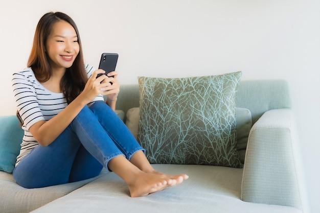 Bella giovane donna asiatica del ritratto che per mezzo o parlando del telefono cellulare