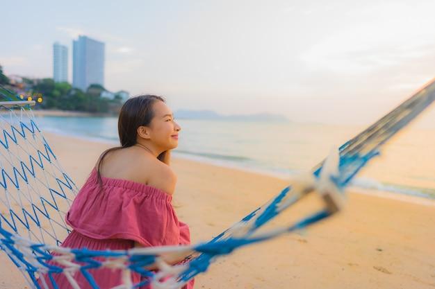 Bella giovane donna asiatica del ritratto che si siede sull'amaca con il mare ed il oce felici vicini della spiaggia di sorriso