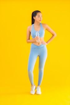 Bella giovane donna asiatica del ritratto con acqua di bottiglia su giallo
