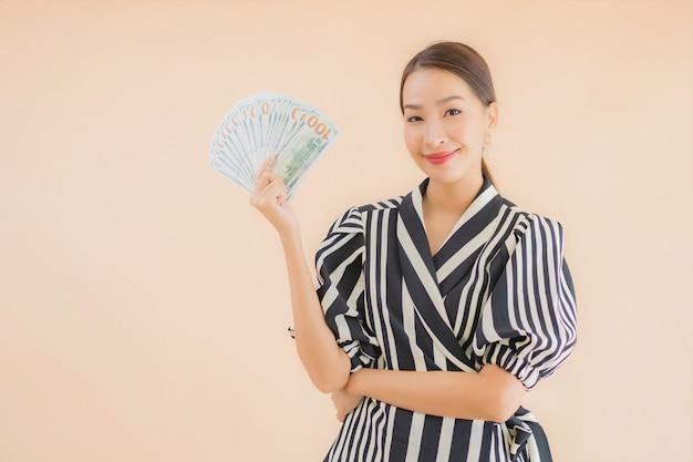 Bella giovane donna asiatica del ritratto con contanti e soldi