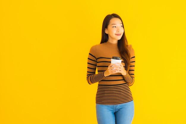 Bella giovane donna asiatica del ritratto con il bagpack e la tazza di caffè in sua mano sulla parete gialla