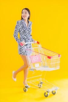 Bella giovane donna asiatica del ritratto con il carrello per la spesa di drogheria sul giallo