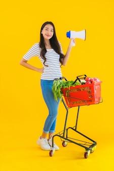 Bella giovane donna asiatica del ritratto con il carretto ed il megafono del canestro della drogheria