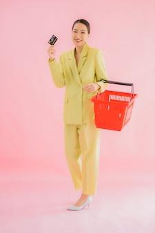 Bella giovane donna asiatica del ritratto con il cestino della drogheria dal supermercato sul colore