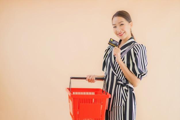 Bella giovane donna asiatica del ritratto con il cestino della spesa