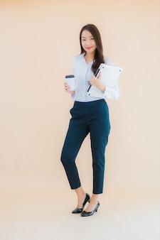 Bella giovane donna asiatica del ritratto con il computer portatile del computer per lavoro