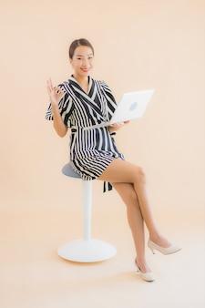 Bella giovane donna asiatica del ritratto con il computer portatile o il computer