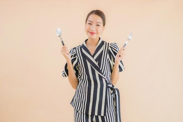Bella giovane donna asiatica del ritratto con il cucchiaio e la forchetta