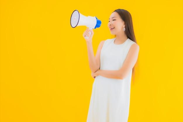Bella giovane donna asiatica del ritratto con il megafono