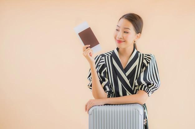 Bella giovane donna asiatica del ritratto con il passaporto della borsa dei bagagli