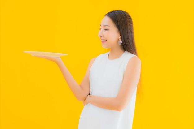 Bella giovane donna asiatica del ritratto con il piatto e il piatto vuoti