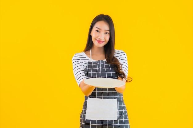 Bella giovane donna asiatica del ritratto con il piatto o il piatto bianco
