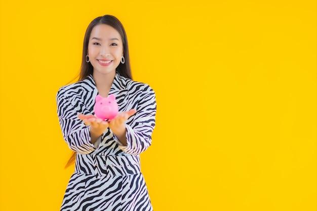 Bella giovane donna asiatica del ritratto con il porcellino salvadanaio e contanti o soldi su giallo