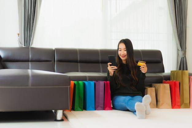 Bella giovane donna asiatica del ritratto con il sacchetto della spesa e la carta di credito
