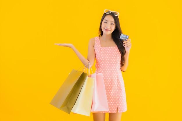 Bella giovane donna asiatica del ritratto con il sacchetto della spesa variopinto con la carta di credito