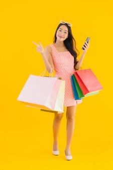 Bella giovane donna asiatica del ritratto con il sacchetto della spesa variopinto con lo smartphone