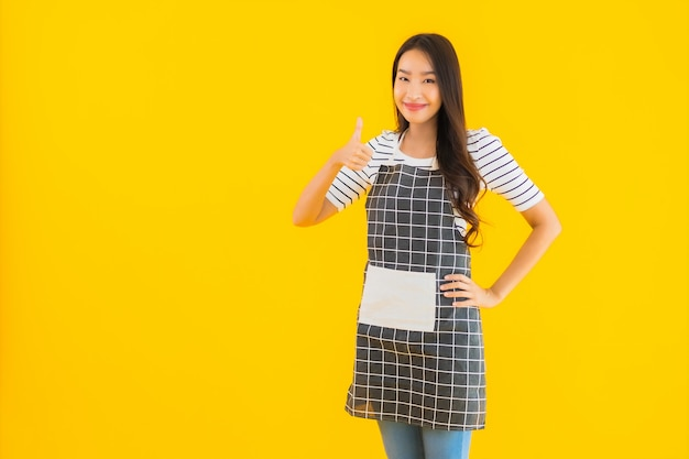 Bella giovane donna asiatica del ritratto con il sorriso del grembiule felice