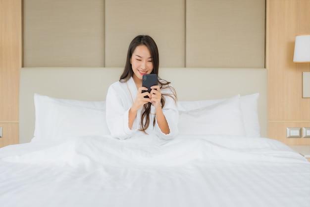 Bella giovane donna asiatica del ritratto con il telefono cellulare astuto in camera da letto