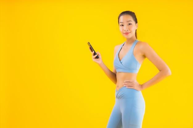 Bella giovane donna asiatica del ritratto con il telefono cellulare astuto su giallo isolato