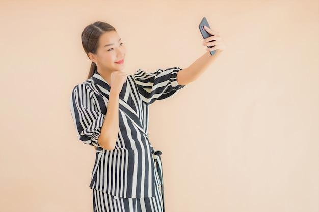 Bella giovane donna asiatica del ritratto con il telefono cellulare astuto