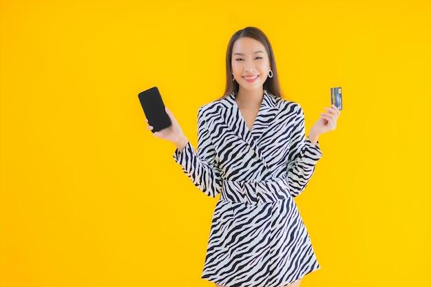 Bella giovane donna asiatica del ritratto con il telefono cellulare e la carta di credito astuti su giallo