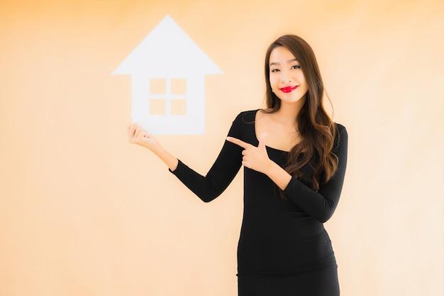 Bella giovane donna asiatica del ritratto con l'insegna domestica