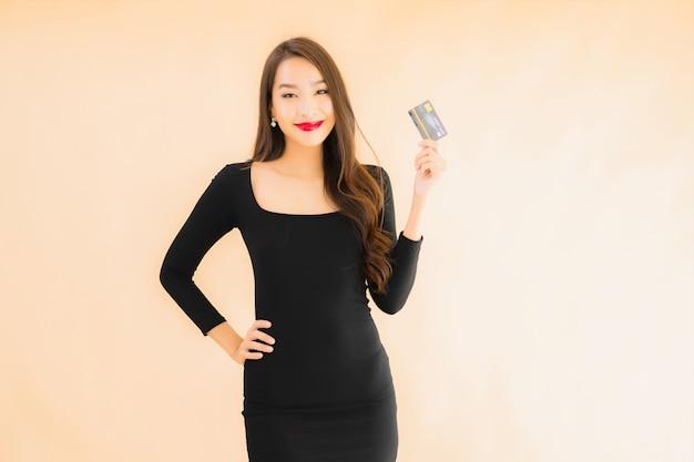 Bella giovane donna asiatica del ritratto con la carta di credito