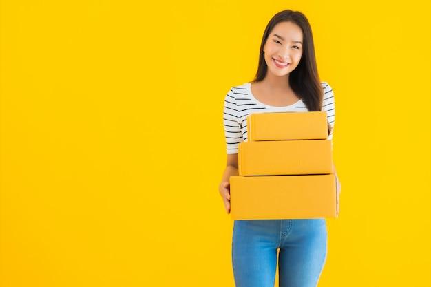 Bella giovane donna asiatica del ritratto con la scatola del pacchetto pronta per spedire