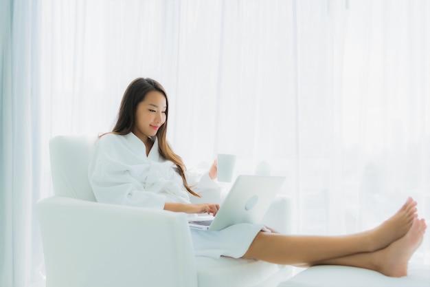 Bella giovane donna asiatica del ritratto con la tazza di caffè e del computer portatile