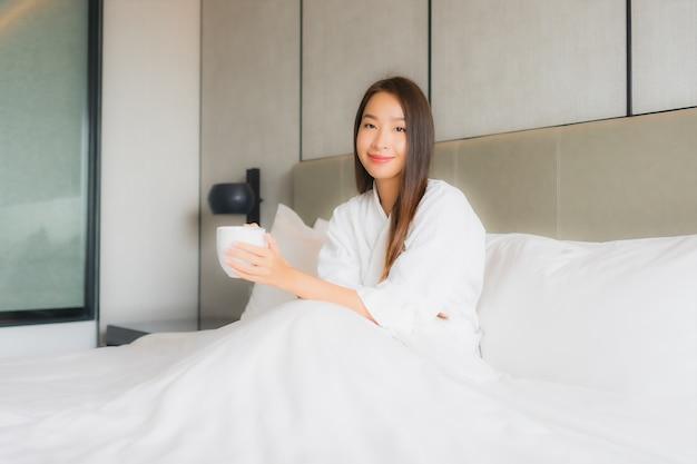 Bella giovane donna asiatica del ritratto con la tazza di caffè in camera da letto