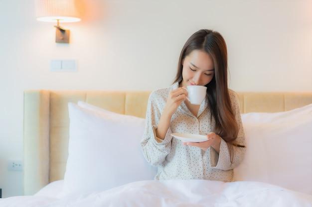 Bella giovane donna asiatica del ritratto con la tazza di caffè sul letto