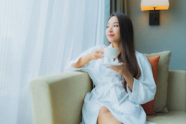 Bella giovane donna asiatica del ritratto con la tazza di caffè sul sofà