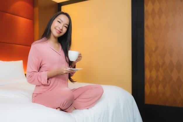 Bella giovane donna asiatica del ritratto con la tazza di caffè sull'interno della decorazione del letto della camera da letto