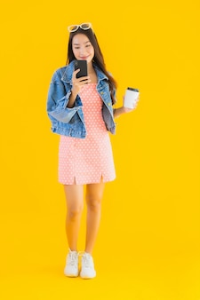 Bella giovane donna asiatica del ritratto con la tazza e lo smartphone di caffè