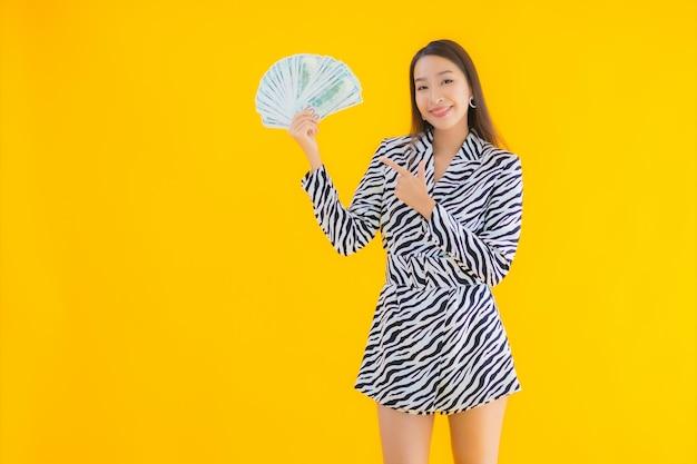 Bella giovane donna asiatica del ritratto con molti contanti e soldi su giallo