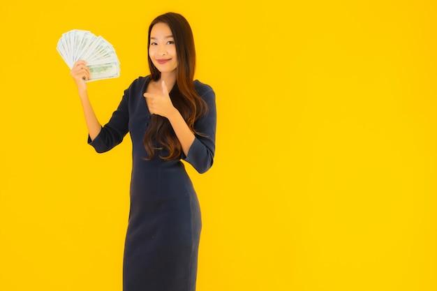 Bella giovane donna asiatica del ritratto con soldi e contanti