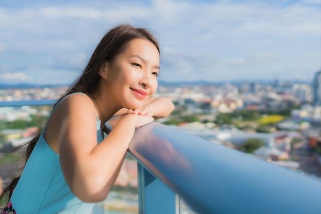 Bella giovane donna asiatica del ritratto intorno al balcone con vista esterna