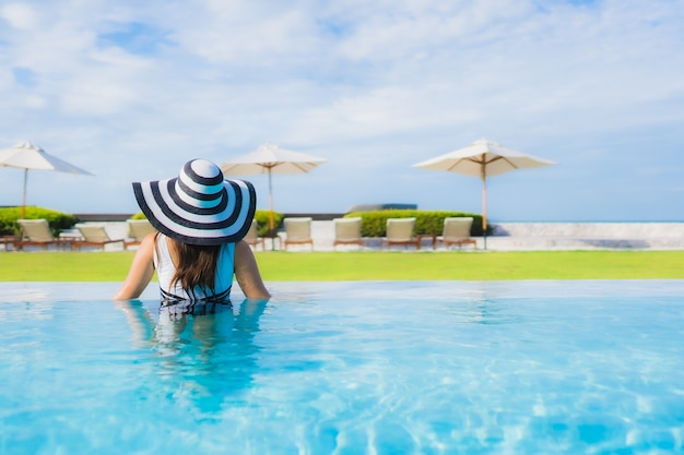 Bella giovane donna asiatica del ritratto intorno alla piscina