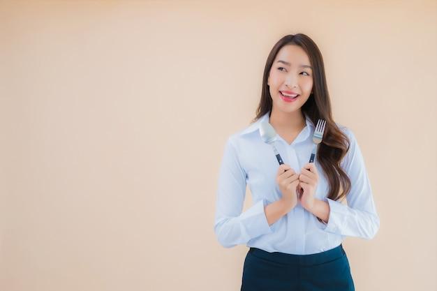 Bella giovane donna asiatica di affari del ritratto con il cucchiaio e la forchetta pronti da mangiare