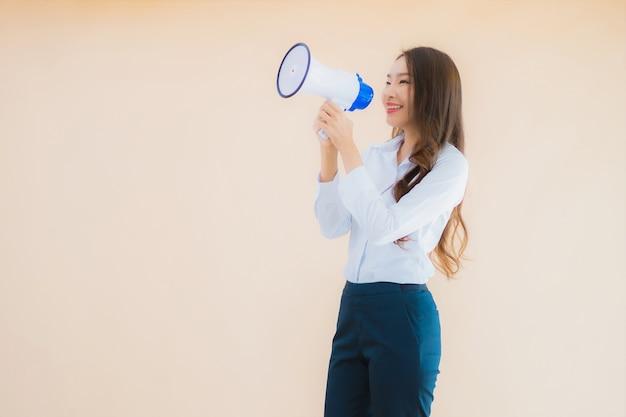 Bella giovane donna asiatica di affari del ritratto con il megafono per cummunication