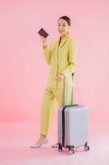 Bella giovane donna asiatica di affari del ritratto con la borsa ed il passaporto dei bagagli sul colore