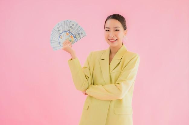 Bella giovane donna asiatica di affari del ritratto con molti contanti o soldi sul colore