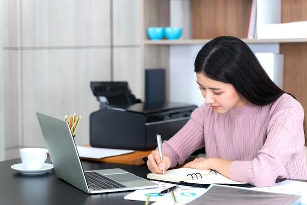 Bella giovane donna asiatica di affari di stile di vita che per mezzo del computer portatile sulla scrivania
