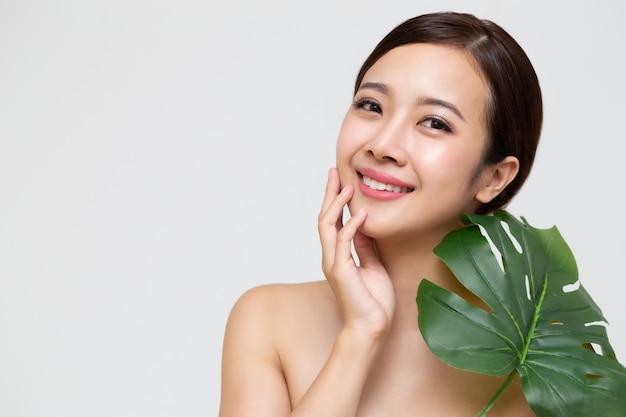 Bella giovane donna asiatica felice con pelle fresca pulita e foglie verdi, cura del viso di bellezza della ragazza, trattamento facciale e concetto della stazione termale di cosmetologia