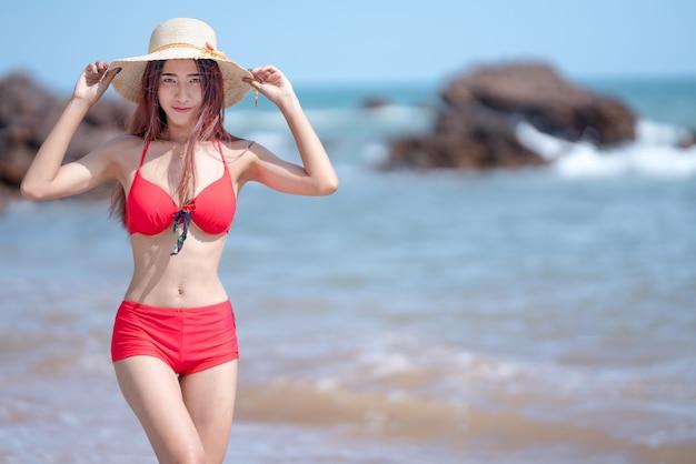 Bella giovane donna asiatica in bikini che si rilassa sulla spiaggia di sabbia, concetto all'aperto di vacanze estive di viaggio