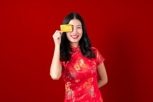 Bella giovane donna asiatica indossa un abito tradizionale cinese rosso con la mano che tiene la carta di credito per mostrare fiducia e sicurezza per effettuare il pagamento su grigio